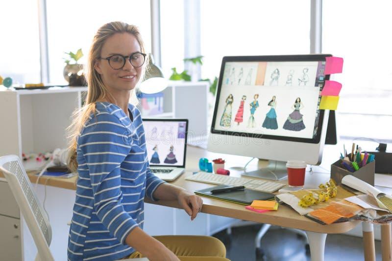 Kvinnlig modeformgivare som ser kameran, medan sitta på skrivbordet i ett modernt kontor royaltyfria foton