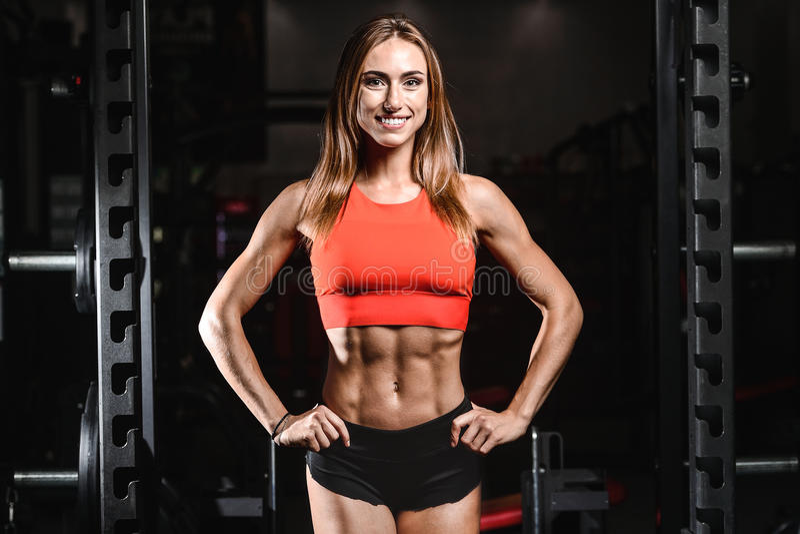 Kvinnlig modell för Caucasian sexig kondition i idrottshallslut upp abs royaltyfria bilder