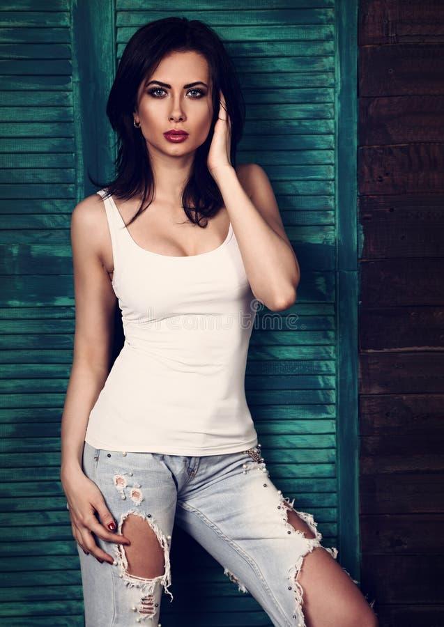 Kvinnlig modell för härlig makeup i moderiktig vit tillfällig överkant, blått r arkivfoto