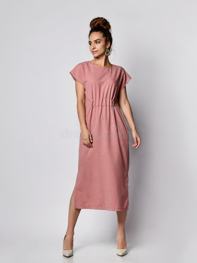 Kvinnlig modell i ett siden- blekt - rosa lång klänning som ser den oavkortade tillväxten för kamera Den nätta flickan i romantis royaltyfri fotografi