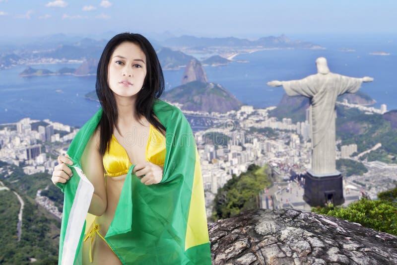 Kvinnlig modell med bikinin och flaggan av Brasilien arkivfoton