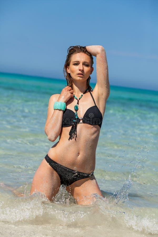Kvinnlig modell som bär den svarta bikinin i vattnet royaltyfria foton