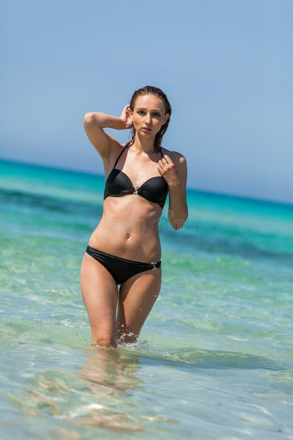 Kvinnlig modell som bär den svarta bikinin i vattnet arkivfoton