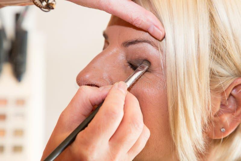 Kvinnlig modell som har ögonmakeup att appliceras av kosmetologen arkivfoton