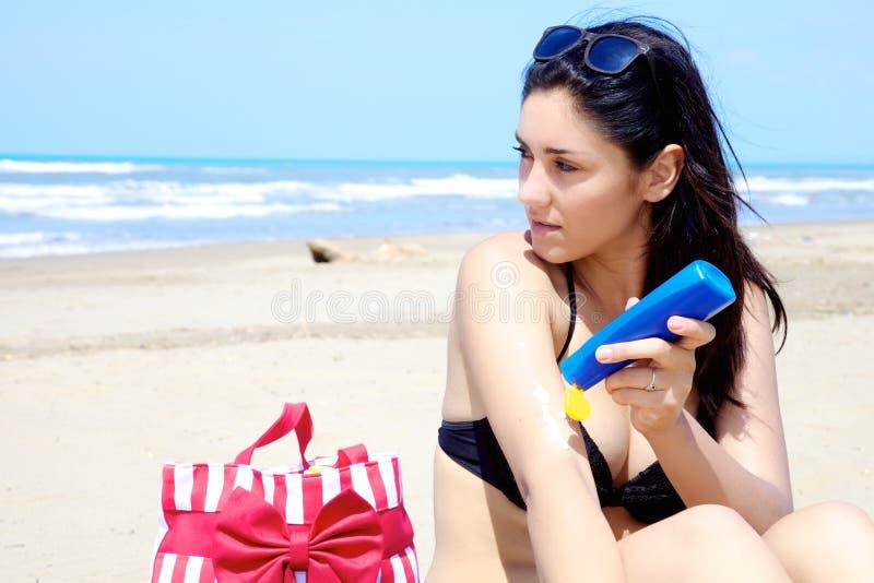 Kvinnlig modell som poserar med solkräm på den soliga stranden royaltyfri fotografi