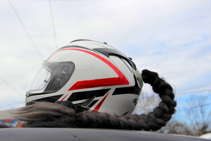 Kvinnlig motorcykelhjälm för en sportcykel med en lie mot den blåa himlen royaltyfri foto
