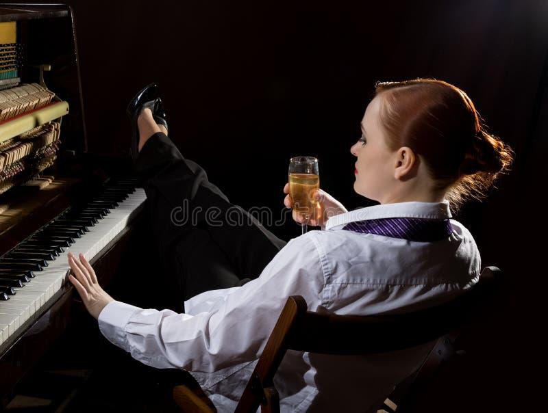 Kvinnlig musiker som är iklädd ett sammanträde för dräkt för man` s bredvid pianot och drinkchampagnen royaltyfri bild