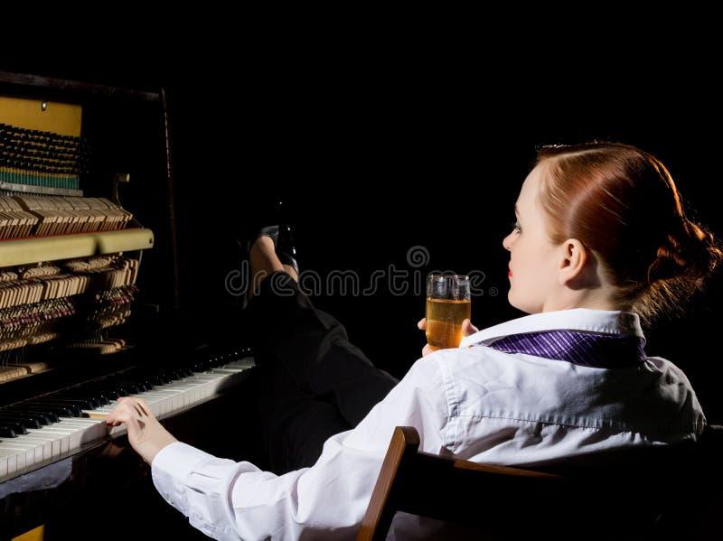 Kvinnlig musiker som är iklädd ett sammanträde för dräkt för man` s bredvid pianot och drinkchampagnen royaltyfri fotografi