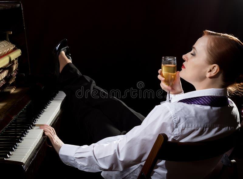 Kvinnlig musiker som är iklädd ett sammanträde för dräkt för man` s bredvid pianot och drinkchampagnen arkivbild