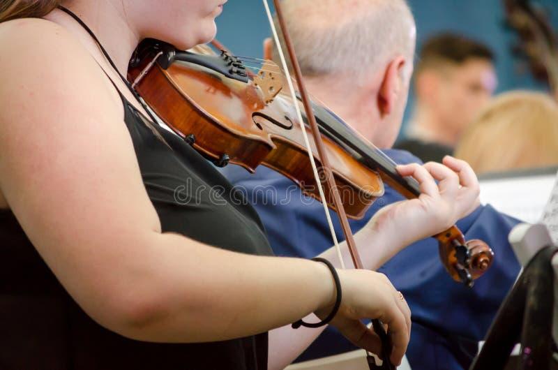 Kvinnlig musiker som spelar en fiol med en symfoniorkester arkivfoto