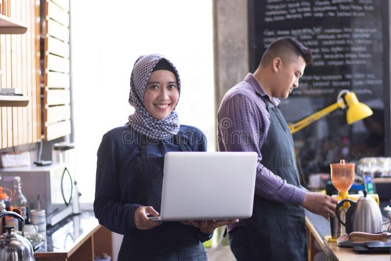 Kvinnlig muslimsk kaféägare på hans coffee shopinnehavbärbar dator och hans partneranseende bak henne som arbetar en beställning  arkivfoto