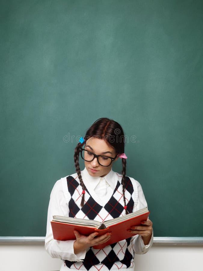 Kvinnlig nerdläsebok arkivfoto