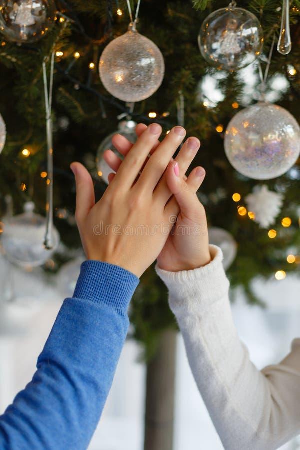 Kvinnlig och manlig hand på bakgrunden av en julgran med leksaker Unga par som tillsammans rymmer händer i dekorerad jul r arkivbild