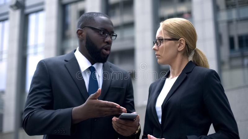 Kvinnlig och manliga affärskollegor som diskuterar sista nyheterna, genom att använda smartphoneappen arkivfoton