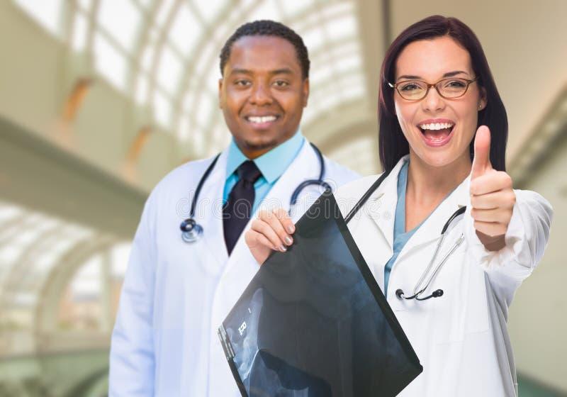 Kvinnlig och manliga caucasian- och afrikansk amerikandoktorer i Hospit royaltyfria bilder