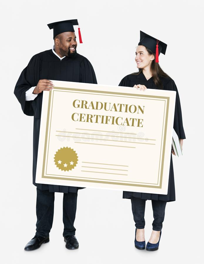 Kvinnlig och manligt akademikert innehav som en avläggande av examen tilldelar intyg arkivfoton