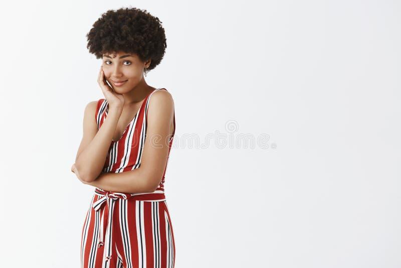 Kvinnlig och modebegrepp för skönhet, Inomhus skott av den gulliga och mjuka afrikansk amerikankvinnan med afro luta för frisyr royaltyfri bild