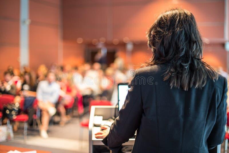Kvinnlig offentlig högtalare som ger samtal på affärshändelsen arkivfoto