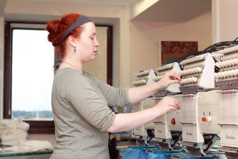 Kvinnlig operatör av automatiska broderimaskiner royaltyfri fotografi