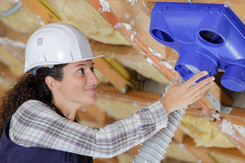 Kvinnlig operatör som kontrollerar betingande rör för luft arkivfoto