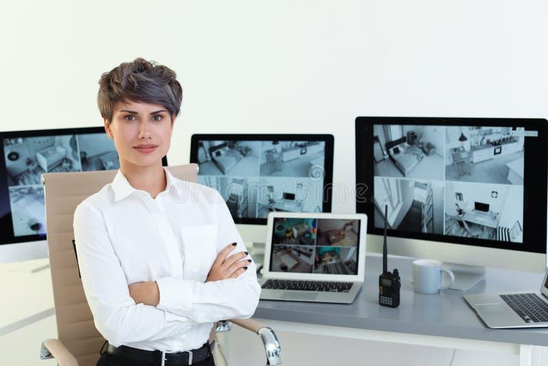 Kvinnlig ordningsvakt på arbetsplatsen med moderna datorer royaltyfria foton