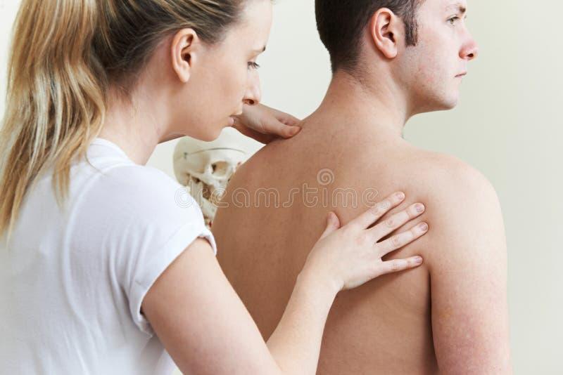 Kvinnlig osteopat som behandlar den manliga patienten med skuldraproblem royaltyfri bild