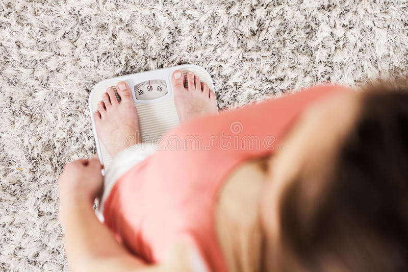 Kvinnlig på skala som mäter viktförlust arkivfoton