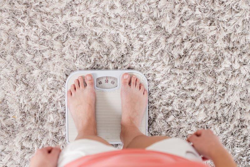 Kvinnlig på skala som mäter viktförlust royaltyfria bilder