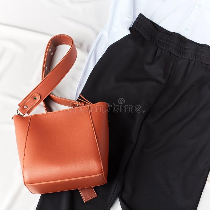 Kvinnlig påse för rött läder, svarta flåsanden, vit blus för kontorsarbetare royaltyfri bild