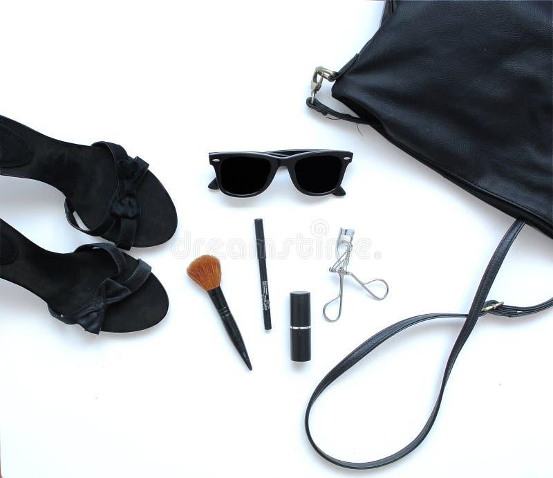Kvinnlig påse med skönhetsmedel, solglasögon och skor royaltyfria bilder