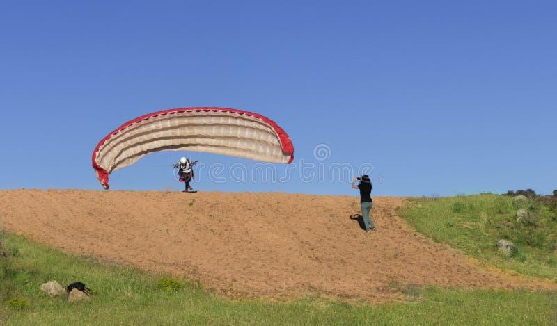 Kvinnlig paragliderpilot som tar av, och kvinna som filmar med hennes mobil royaltyfri fotografi