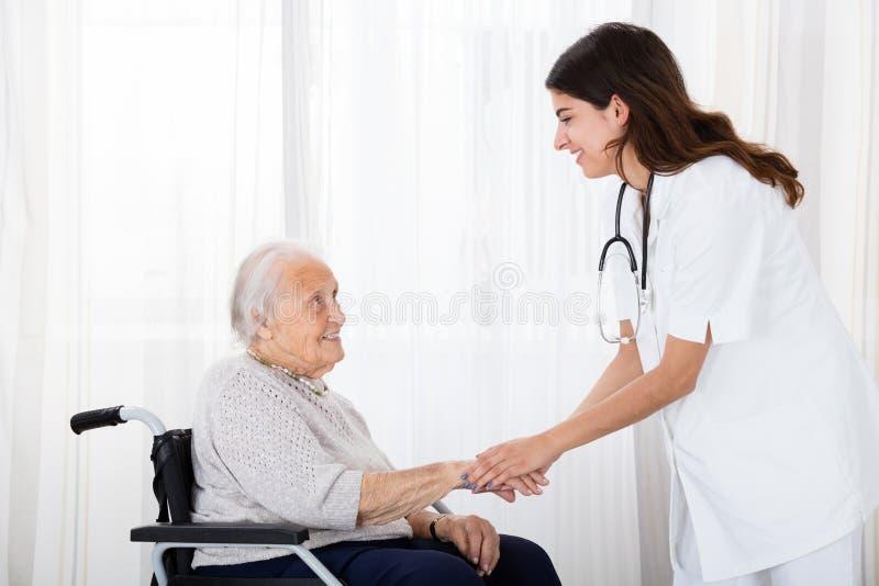 Kvinnlig patient för doktor Consoling Disabled Senior royaltyfri fotografi