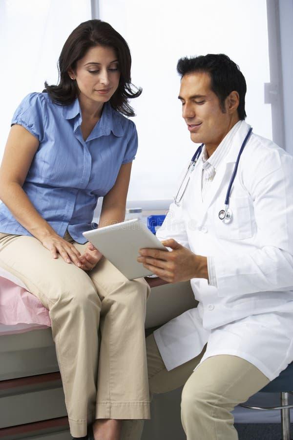 Kvinnlig patient för doktor som In Surgery With diskuterar anmärkningar på den Digital minnestavlan fotografering för bildbyråer
