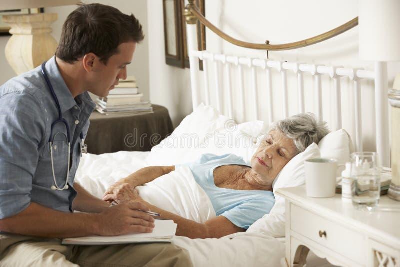 Kvinnlig patient för doktor Talking With Senior i säng hemma royaltyfri bild