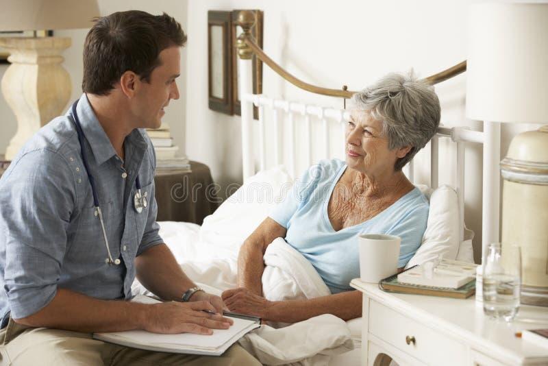Kvinnlig patient för doktor Talking With Senior i säng hemma arkivbild