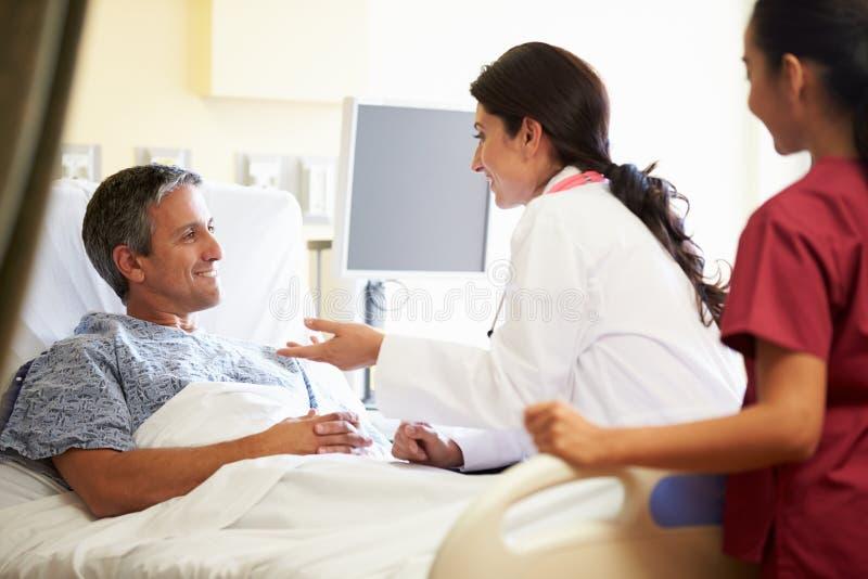 Kvinnlig patient för doktor Talking To Male i sjukhusrum royaltyfri fotografi
