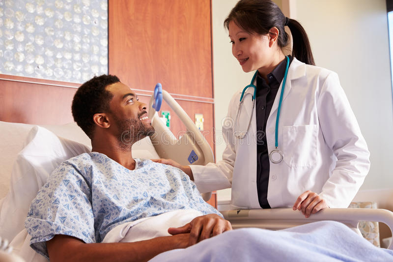 Kvinnlig patient för doktor Talking To Male i sjukhussäng fotografering för bildbyråer