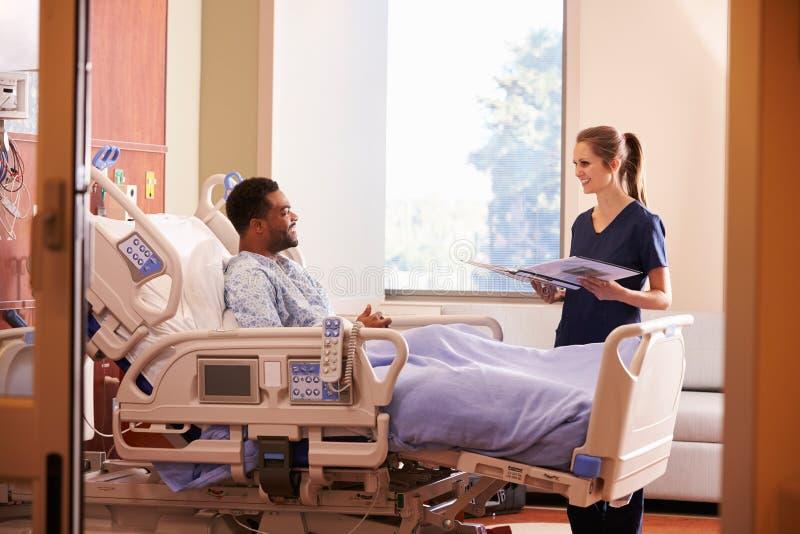Kvinnlig patient för doktor Talking To Male i sjukhussäng royaltyfri foto