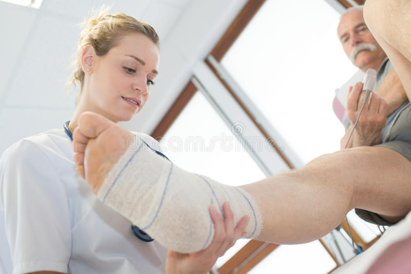 Kvinnlig patient för doktorshandlagfot royaltyfri bild