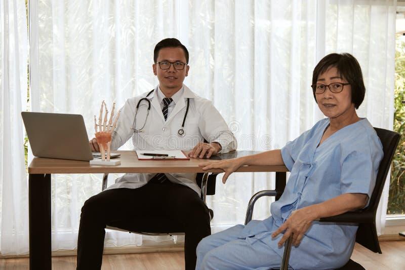 Kvinnlig patient för fläder att konsultera med den smarta ortopediska doktorn arkivbilder