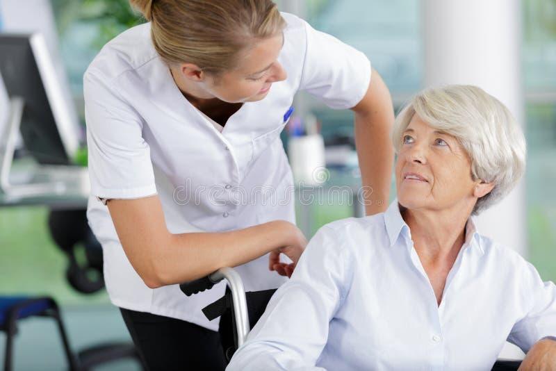 Kvinnlig patient f?r doktor With Disabled Senior i sjukhus arkivfoton