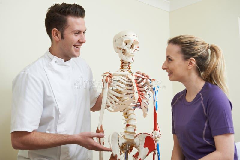 Kvinnlig patient i konsultation med osteopaten fotografering för bildbyråer