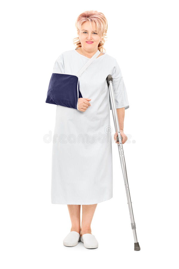 Kvinnlig patient med brutet armanseende med en krycka arkivbild