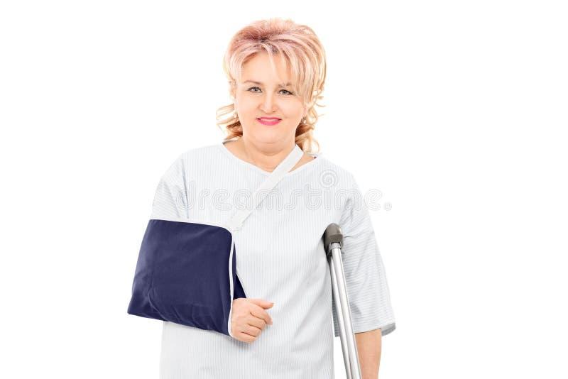 Kvinnlig patient med brutet armanseende med en krycka arkivbilder
