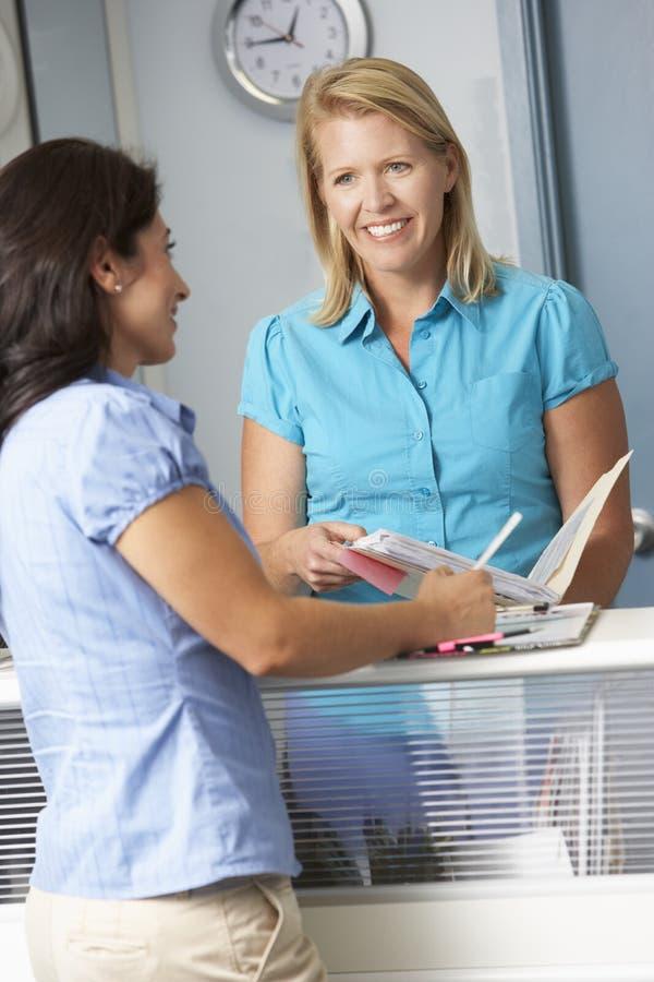 Kvinnlig patient med receptionistIn Doctors Waiting rum arkivbilder