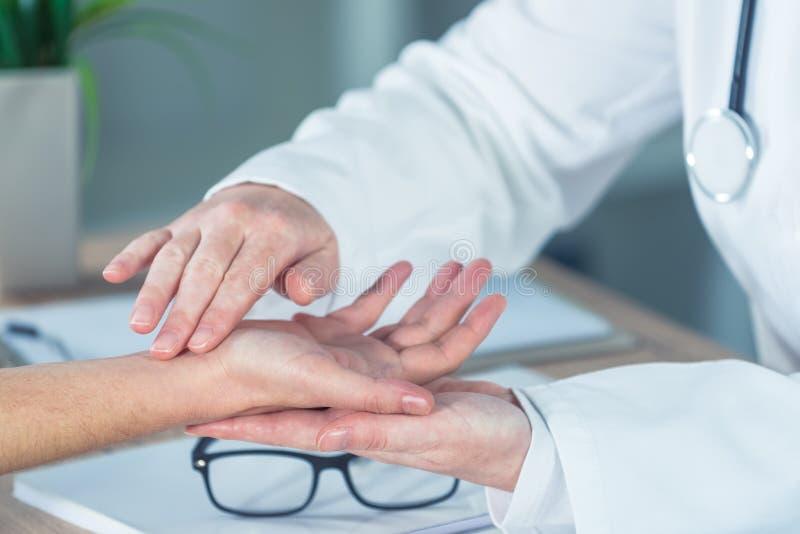 Kvinnlig patient på medicinsk examen för ortopedisk doktor för handledinjur fotografering för bildbyråer