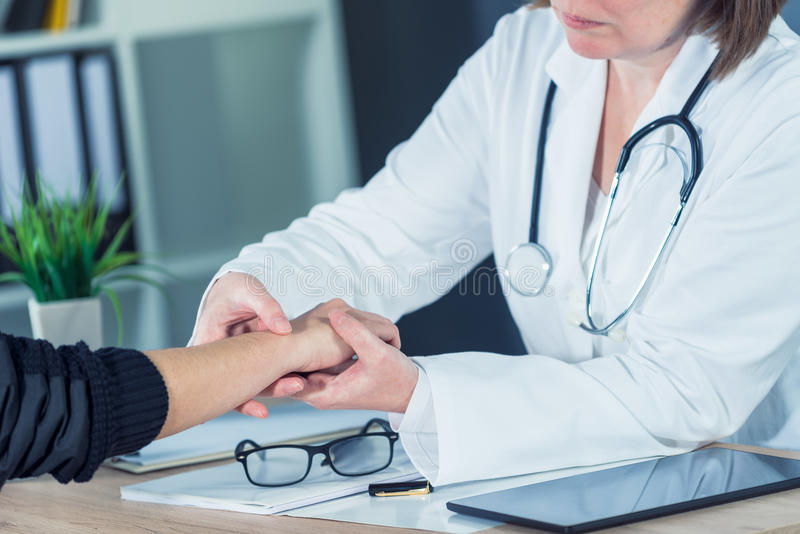 Kvinnlig patient på medicinsk examen för ortopedisk doktor för handledinjur arkivfoto
