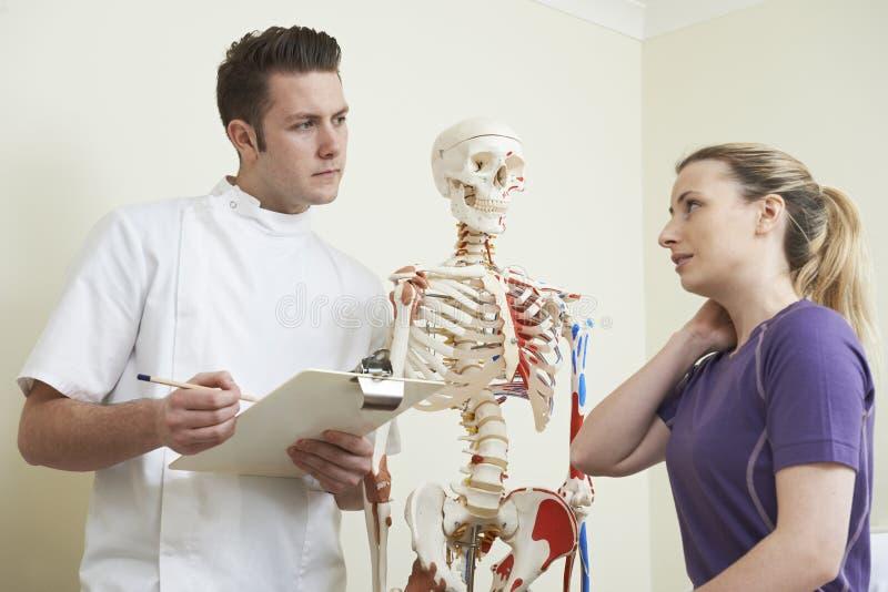 Kvinnlig patient som beskriver halsskada till osteopaten arkivfoto