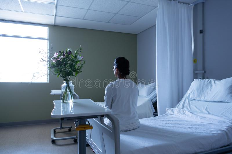 Kvinnlig patient som bort ser, medan sitta på säng royaltyfri bild