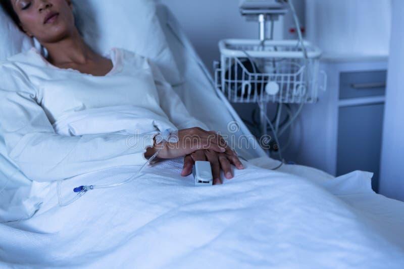 Kvinnlig patient som kopplar av på säng royaltyfria foton